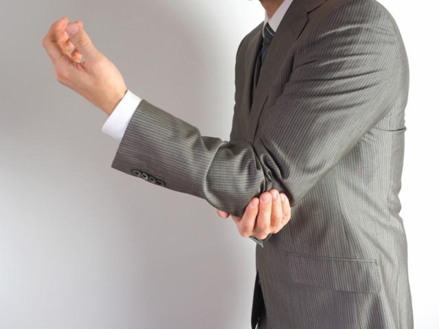 肘を抑える男性の写真